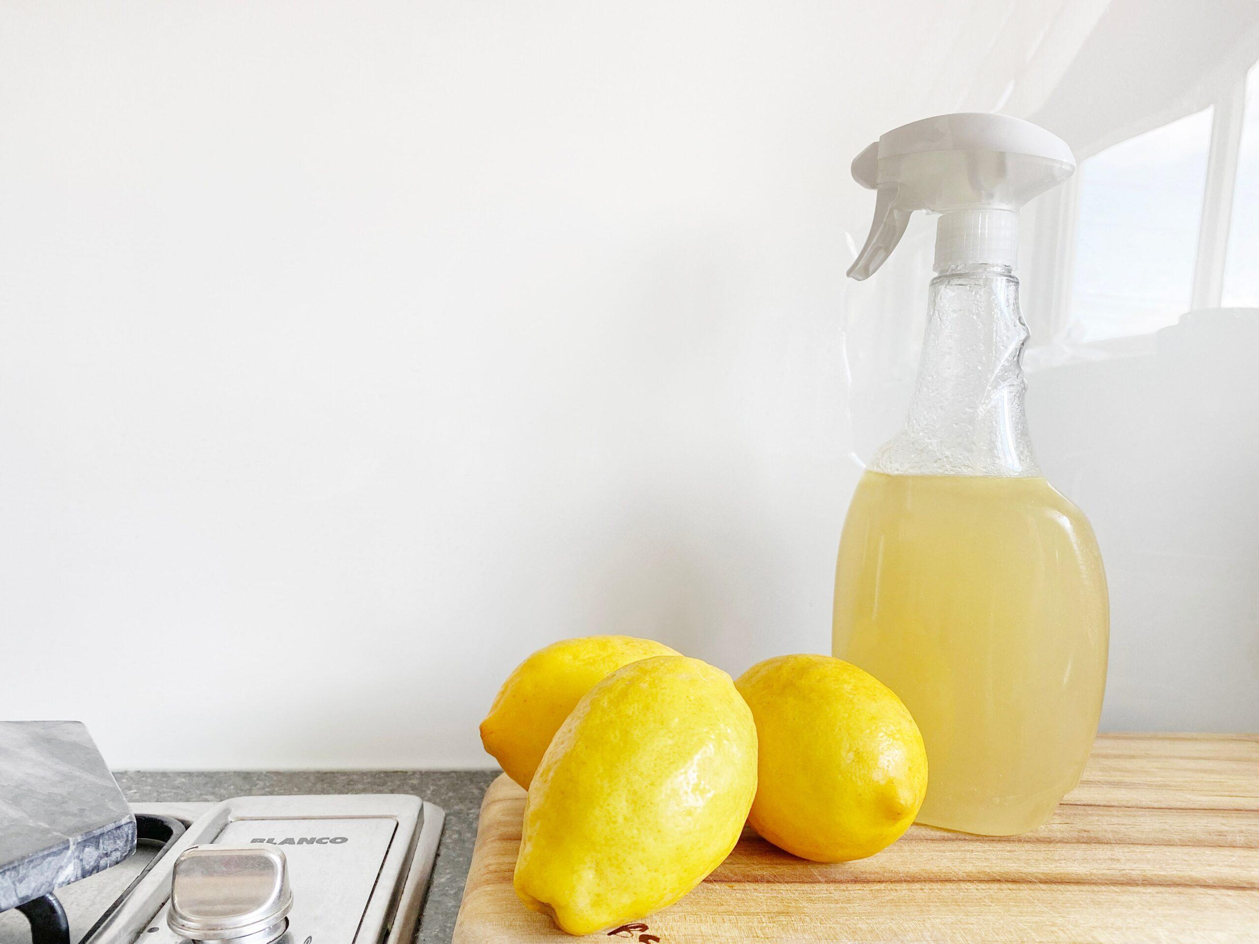 Lemon essential oil in spray bottle with lemons.