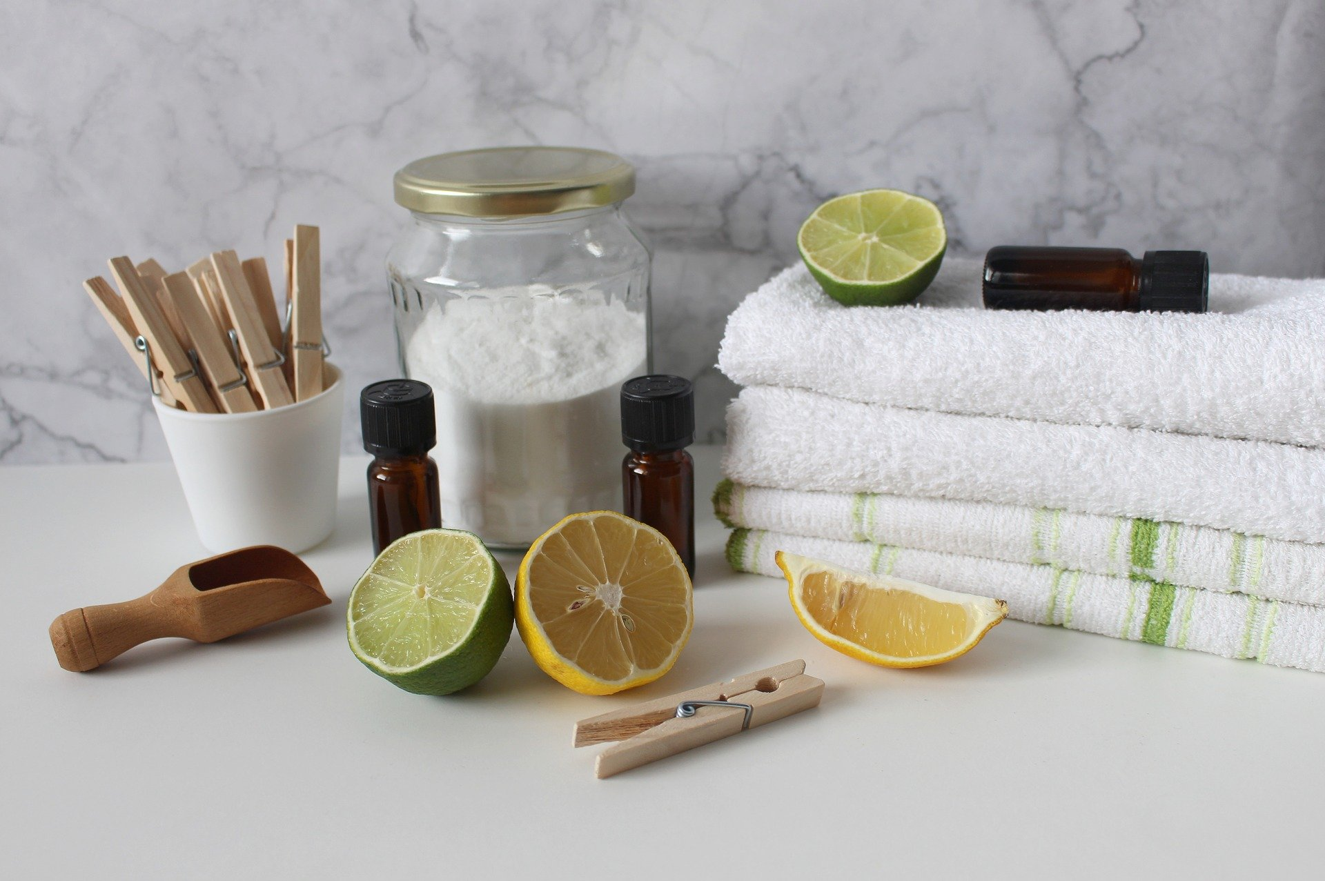 Folded towels, pegs, lemons and limes with essential oil bottles for cleaning.