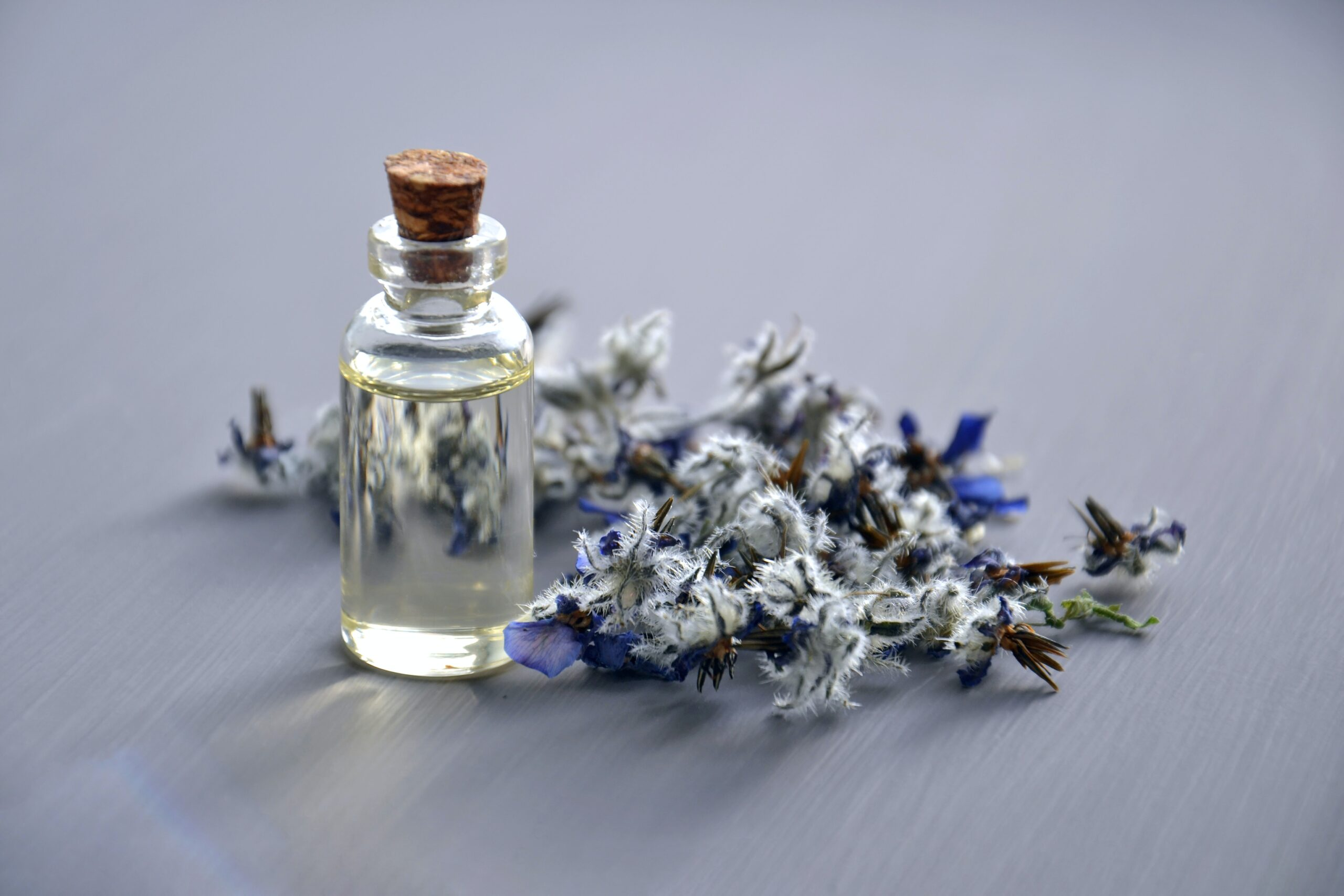 Lavender essential oil in bottle with flowers behind.