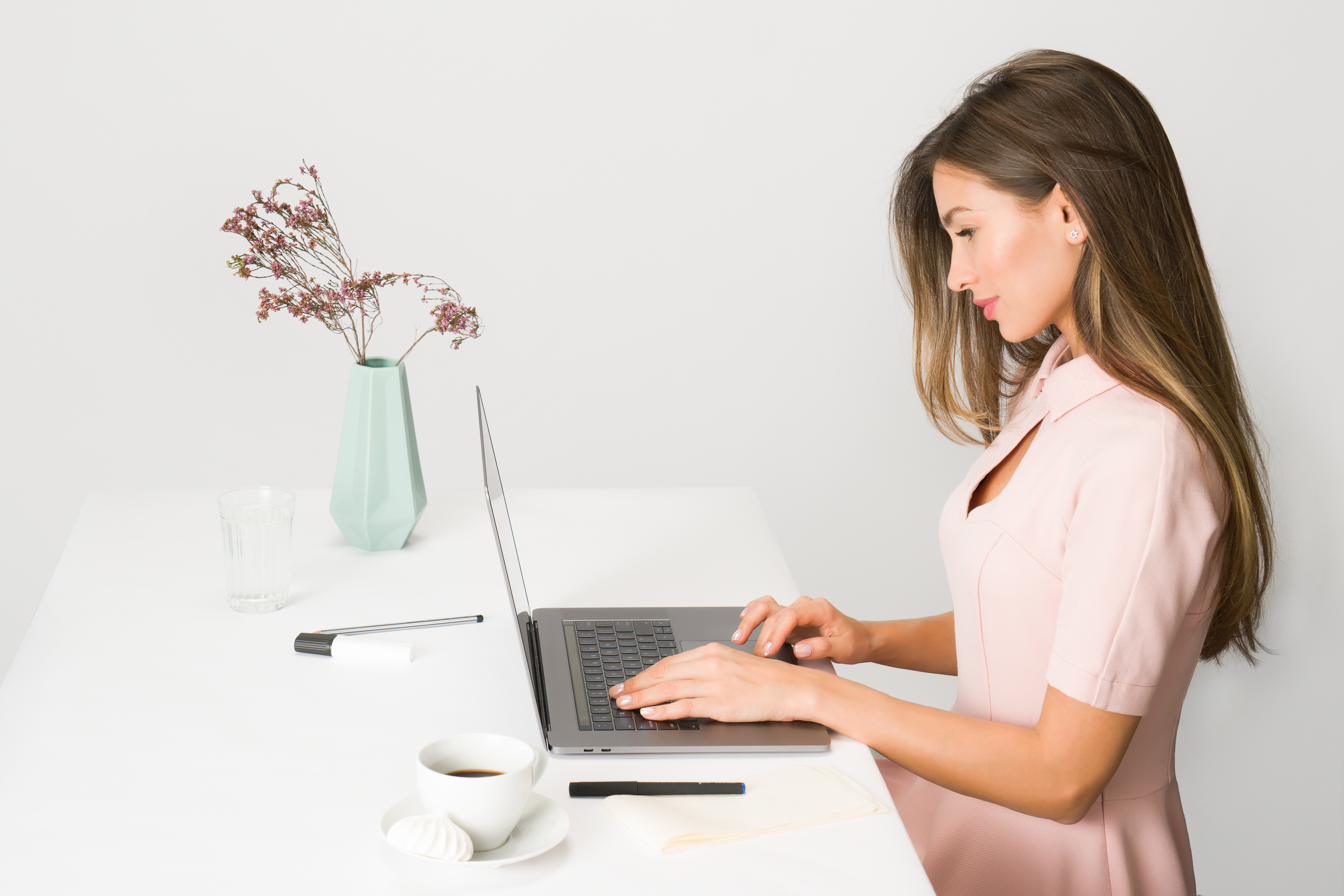 Woman sitting at desk with tea and a laptop reading essential oil reviews.